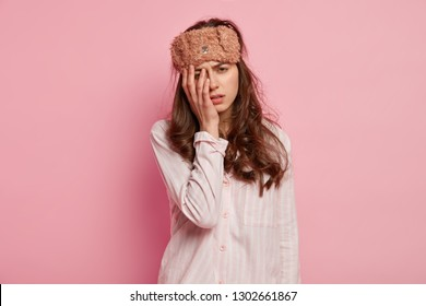 Upset tired young woman has not enough sleep, touches face with hand, wears eyemask and casual jumper, isolated over pink background, slept bad at night. People, tiredness and awakening concept