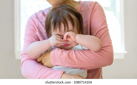 Upset toddler boy crying while being comforted by his mother