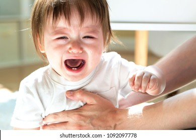 Upset toddler boy crying while being held by his father