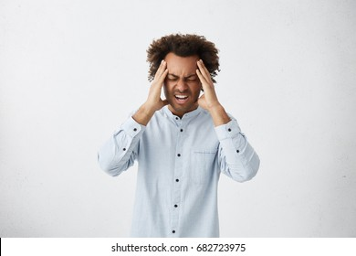 Upset unhappy dark-skinned male student squeezing head with hands, writhing in pain, suffering from headache after he spent sleepless night preparing for exams. People, stress, tension and migraine
