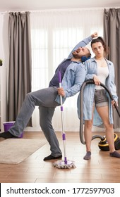 Upset wife with vacuum cleaner because of happy husband while cleaning the apartment.