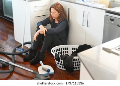 Upset woman (age 30-40) with overload housework sitting on kitchen floor.
