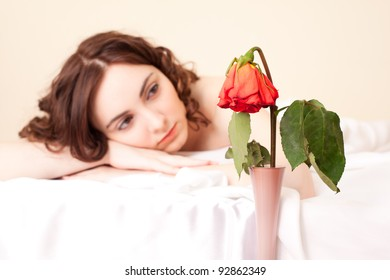 Upset woman in bed looking on the wither  rose (focus on rose)