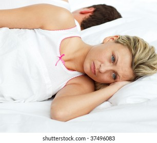 Upset woman in bed sleeping separate of a man