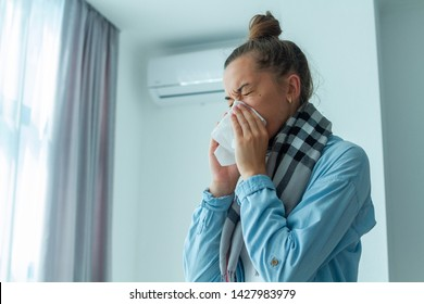 Upset woman caught a cold from the air conditioner and sneezing