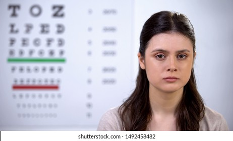 Upset woman checking eye-sight at oculist appointment, vision health problems