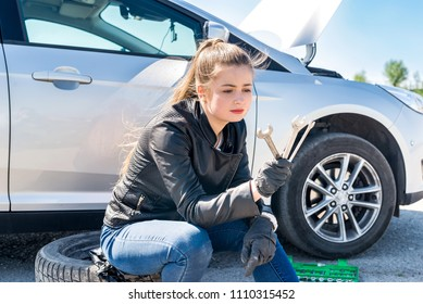 Upset woman with different wrenches and broken car