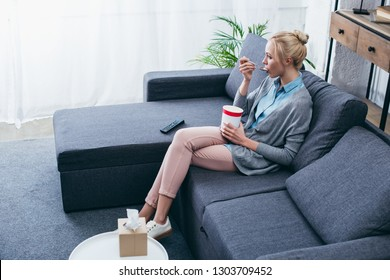 upset woman eating ice cream while siitng on couch at home alone