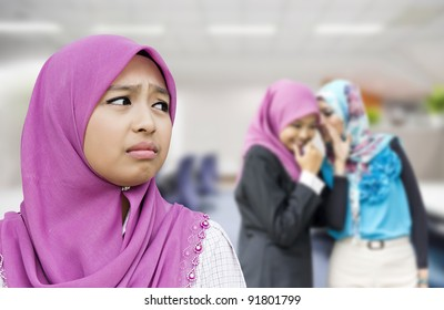 Upset woman with her friends gossiping in background