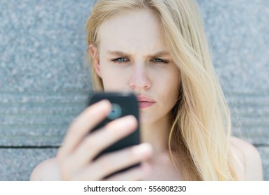 Upset woman holding a cellphone.