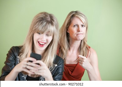 Upset woman with laughing teen on cell phone