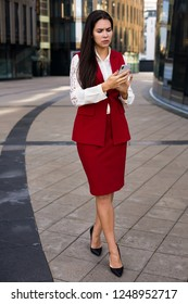 Upset woman leadership dressed in luxury red office wear chatting on mobile phone while walking outdoors near business centre. Disappointed female jurist reading bad news on cellphone