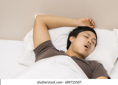 Upset woman lying on bed,  Snoring man. Couple in bed, man snoring and woman can not sleep, for snore noise.