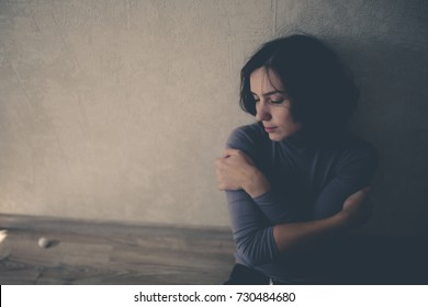 upset woman near the gray wall, concept of depression and loneliness, selective focus and toning