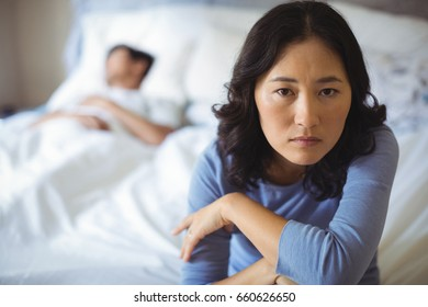 Upset woman sitting on bed in bedroom at home