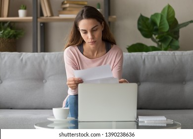 Upset woman sitting on couch at home near computer holding paper reading bad news notification about job rejection, public utility debt, credit refusal letter student failed exam, scholarship concept