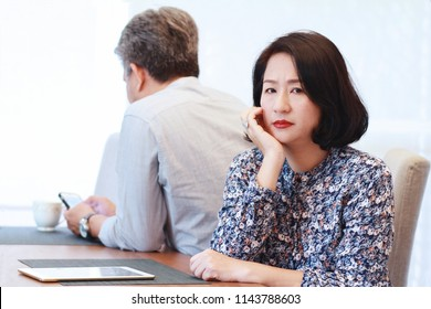 Upset woman sitting on the dining table  with her husband who using mobile phone. 40 s Asian couple  with relationship problem appear depressed and frustrated.Japanese wife depressed.Selective focus.
