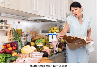 upset woman is standing with paper bag and is sading because forgot to buy ingridient for recipe at home.