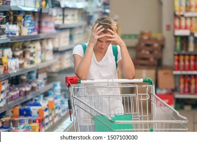 Upset woman in a supermarket with an empty shopping trolley. Crises, rising prices for goods and products. Woman shopping at the supermarket.