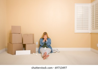 Upset Woman with Tissues on Floor Next to Boxes and Blank Sign in Empty Room.