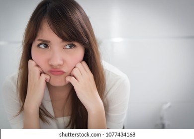upset woman in toilet by diarrhea, constipation, hemorrhoids, piles; portrait of woman hard pushing in toilet or wc from diarrhea, constipation, food poisoning, hemorrhoids; asian adult woman model