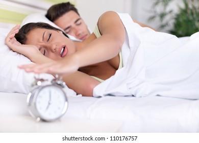 Upset woman turn off alarm clock, Wake up early morning.