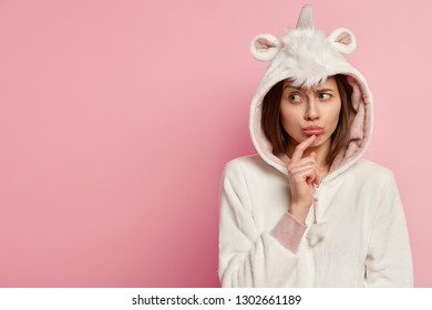 Upset woman wears unicorn costume, has sullen expression, focused aside, purses lips, feels offended by someone, isolated over pink wall with empty space for your promotion. Girl in nightwear