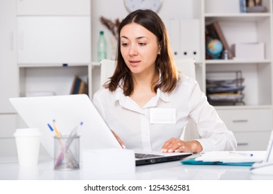 Upset  woman working with laptop and papers at the office  table