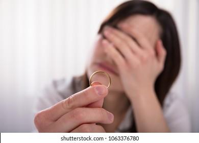 Upset Woman's Hand Holding Wedding Gold Ring