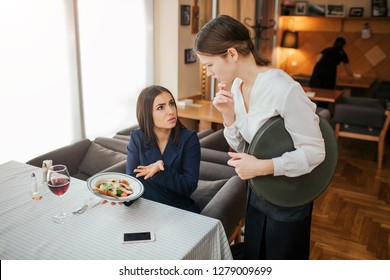 Upset yougn businesswoman complain about bowl with salad. She hold it in hands and point. Customer look at waitress. Young woman in white blouse is upset.