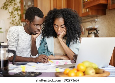 Upset young African-American couple feeling unhappy because they can't afford buying new car, facing financial problem and economic crisis, trying to solve troubles, reviewing their finances at home