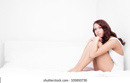 upset young brunette woman sitting on the white linen in bed at home, copyspace for your text to the left