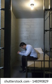 Upset young businessman sitting on bed in prison