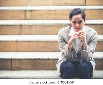 Upset young caucasian beautiful businesswoman tired from work sitting at stairs, unemployment, fired from job, disappointed, loss and feeling down concept