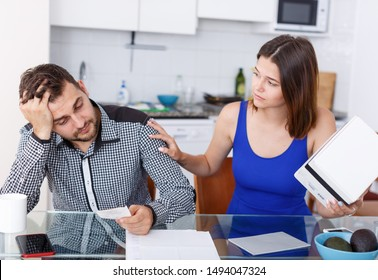 Upset young couple with bill and box having conflict in home interior