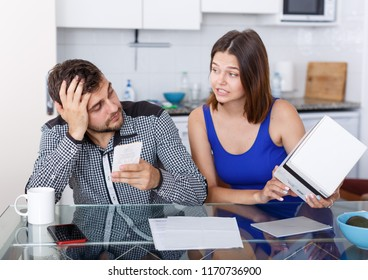 Upset young couple with financial bills and box having conflict at home