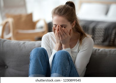 Upset young female sit on couch at home crying over ended relationships, unhappy girl cover face feeling down after breaking up with boyfriend, woman lie on sofa have problems in life