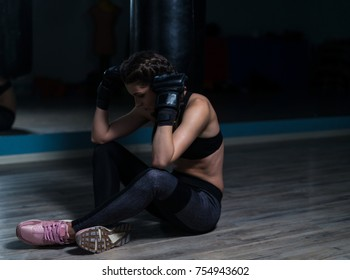 Upset young fighter boxer girl wearing boxing gloves siting on the floor after loosing fight.  She is thinking