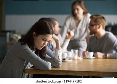 Upset young girl sit alone at coffee table in café feeling lonely or offended, sad female loner avoid talking to people, student outsider suffer from discrimination, lacking friends or company