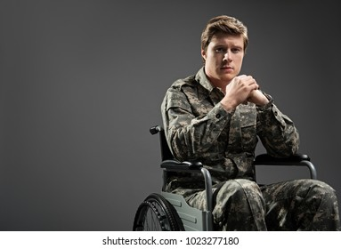 Upset young male looking at camera with sad look. He is sitting in invalid chairing wearing military uniform. Isolated on grey background. Copy space in left side