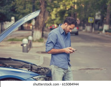 Upset young man calling texting roadside assistance after breaking down