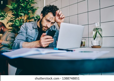 Upset young man with eyeglasses in hand reading business news on website on modern mobile phone using free 4G internet sitting at laptop computer.Pensive hipster guy received warning message from bank