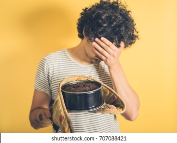 An upset young man is holding a burnt cake