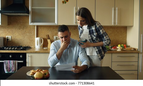 Unpaid images stock photos vectors shutterstock upset young man reading unpaid bills and hugged by his wife supporting him in the kitchen fandeluxe Images