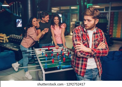 Upset young man stand in front in playing room. He look backwards. His friends standing behind and laughing. They cheerless.