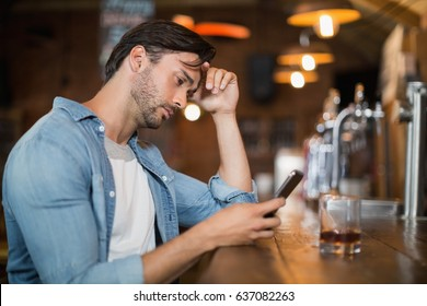 Upset young man using mobile while sitting at pub