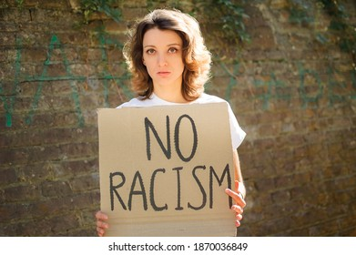 Upset young protesting woman in white shirt holds protest sign broadsheet placard with slogan 'No racism' for public demonstration on stone wall background