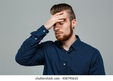 Upset young successful businessman posing over grey background. Copy space.