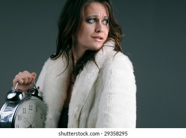 Upset young woman with an alarm clock