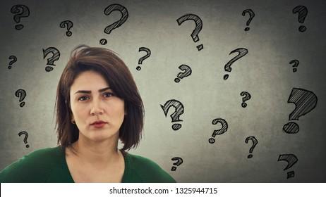 Upset young woman looking serious and sad having questions as interrogation marks like flying around head isolated on gray wall background.